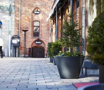 En vacker kruka i ljus- eller mörkgrå aluminium för offentlig utemiljö.