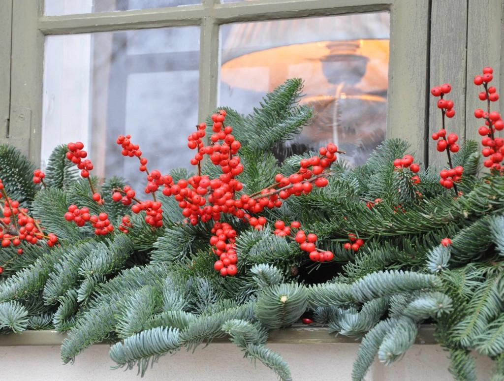 Fönsterpynt med silvergran och röda bär.
