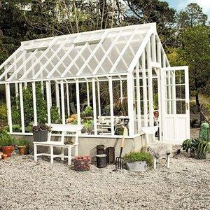 Vackert, svensktillverkat odlingsväxthus med vitmålade träprofiler från Sweden Green House.