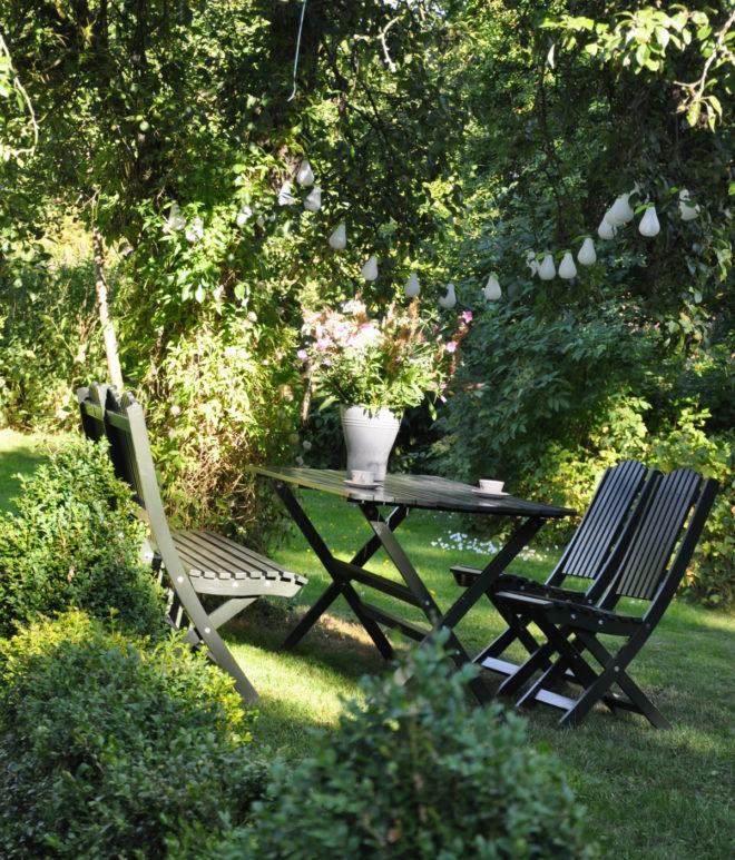 Frodigt sommargrönt med sittplats under päronträdet.