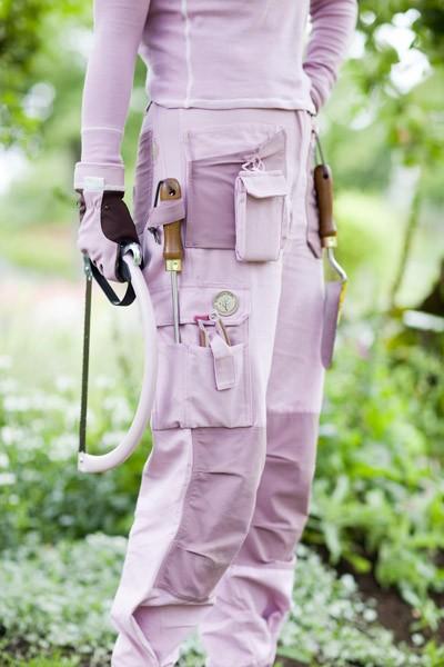 Matchande trädgårdskläder och -redskap i rosa och lila färg.