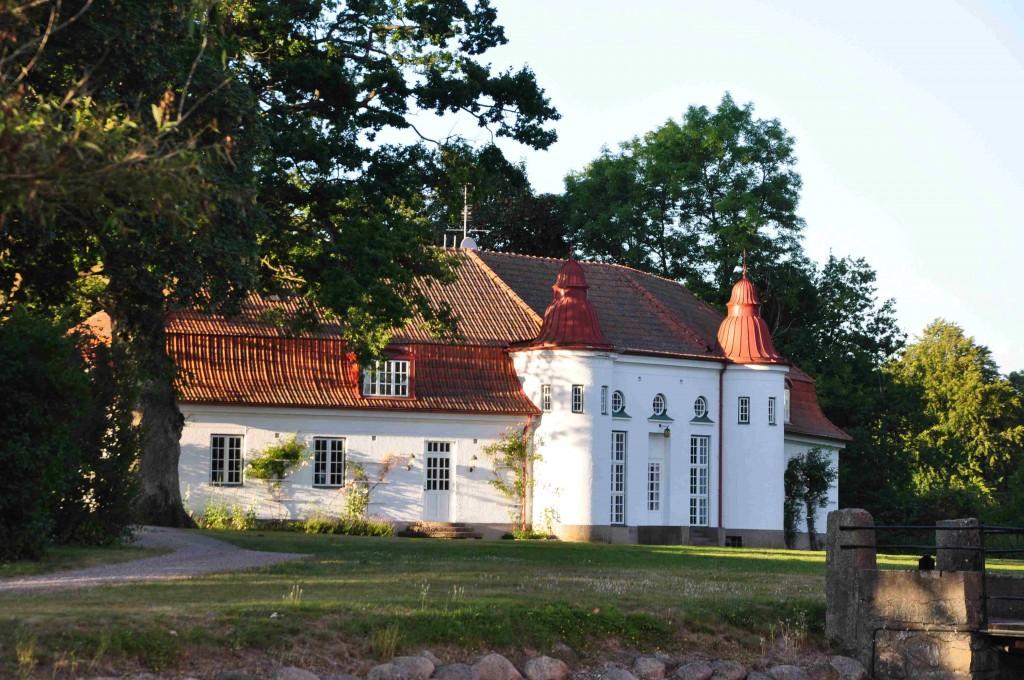 Den vita villan kontrasterar starkt mot den höga slottsbyggnaden.
