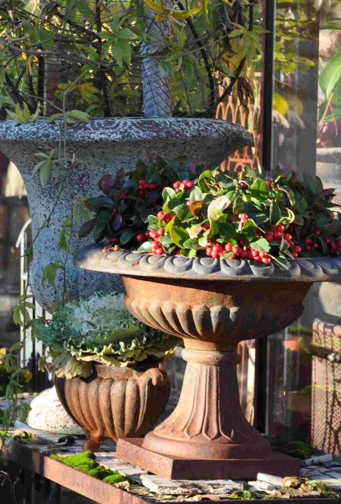 Urnor och krukor i olika patinerade material med matchande blomsterdekorationer.